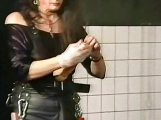 domina wearing leather puts marital-device in the